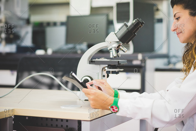 Female scientist using digital tablet and optical microscope