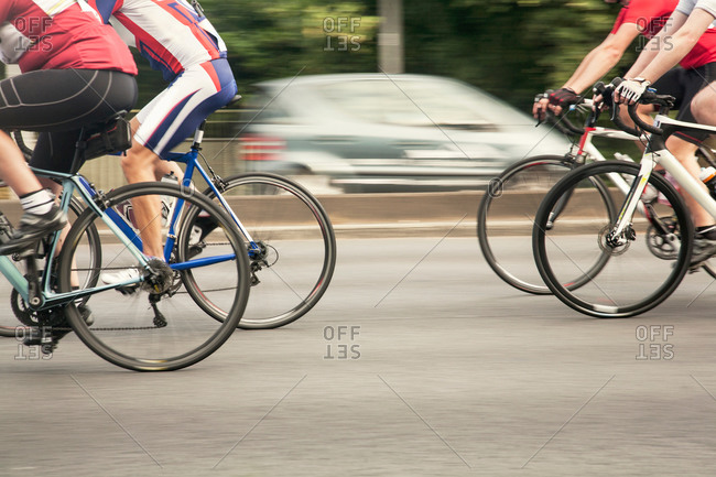 Neck down view of four racing cyclists speeding on urban road in racing cycle race