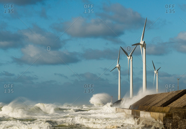 Stormy ocean waves splashing wind turbines on harbor wall, Boulogne-Sur-Mer, Pas de Calais, France