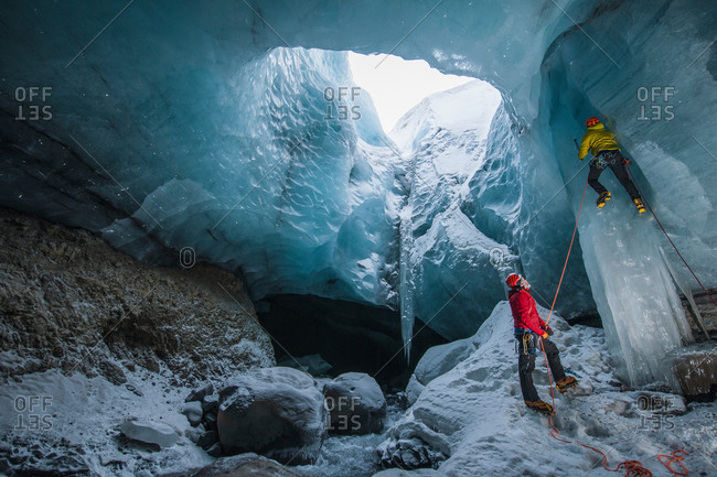 Two ice climbers climbing up ice cave below the Gigjokull glacier, Thorsmork, Iceland