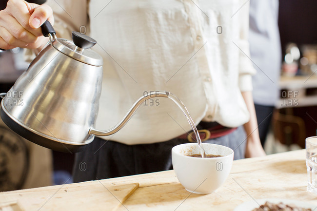 Coffee taster pouring hot water into cup of coffee