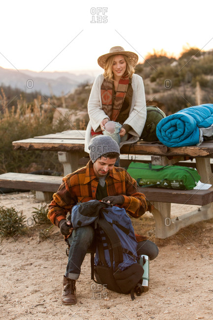 Young couple in rural setting, sorting through camping equipment