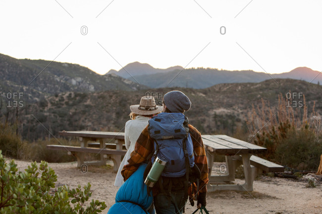 Young couple in rural setting, carrying camping equipment