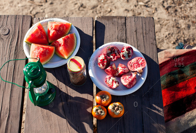 Cut fruit on plates on picnic table, overhead view