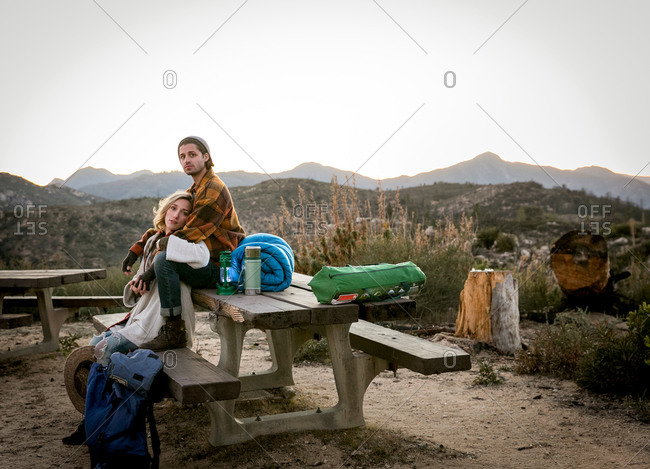 Portrait of young couple sitting on picnic bench in rural setting, young man sitting behind young woman