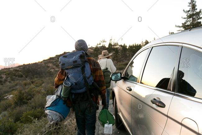 Young couple walking away from parked car carrying camping equipment, rear view