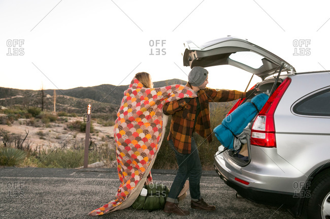 Young couple putting camping equipment in boot of car