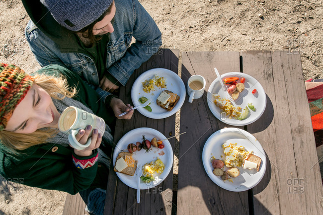 Young couple eating lunch at picnic table, elevated view