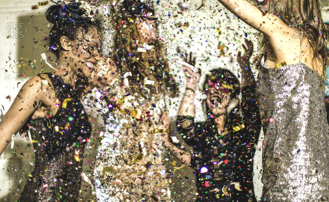 Women dancing together in confetti at a party