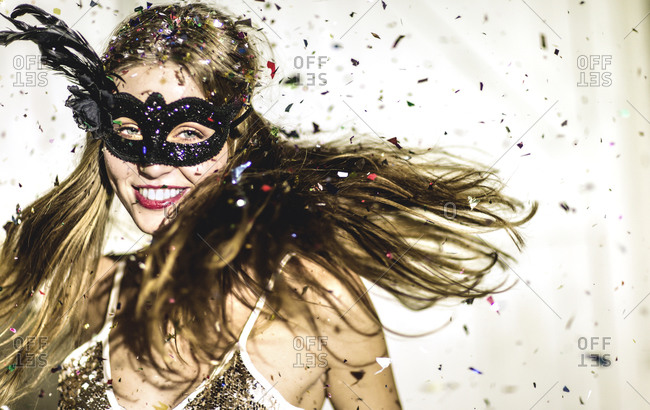Woman in a party mask dancing in confetti