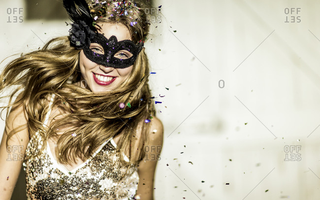 Woman in a party mask standing among confetti