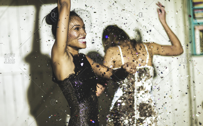Friends celebrating at a party with confetti