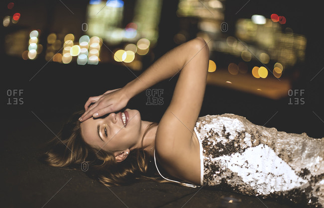 Young woman in a party dress lying on a city rooftop