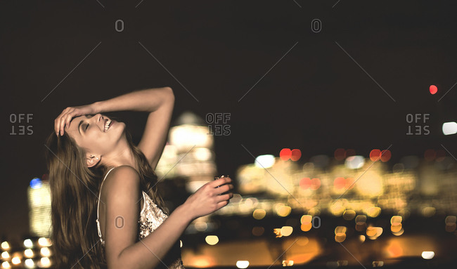 Young woman on a city rooftop taking a shot