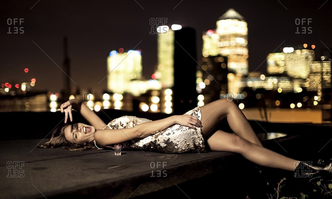 Young woman in a party dress lying down on a city rooftop yelling and giving a peace sign