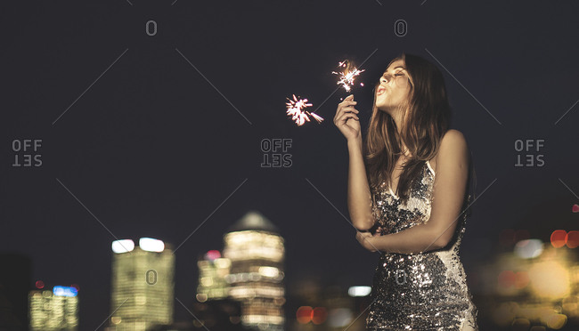 Young woman on a city rooftop holding sparklers
