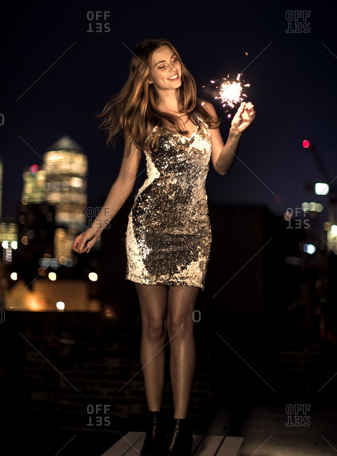 Woman on a city rooftop holding a sparkler and smiling