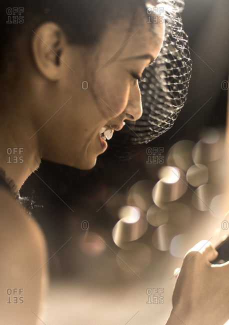 Woman in a party hat smiling among glowing lights