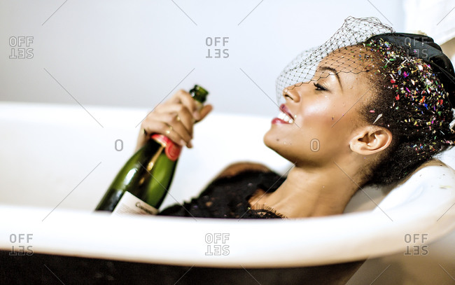 Young woman with confetti in her hair lying in a bathtub with a bottle of champagne