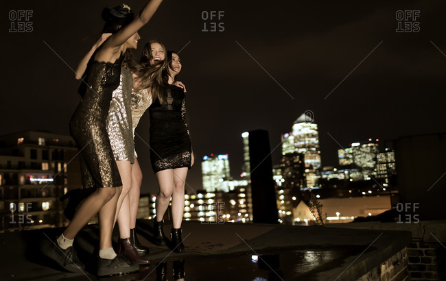 Friends in party dresses standing on a city rooftop