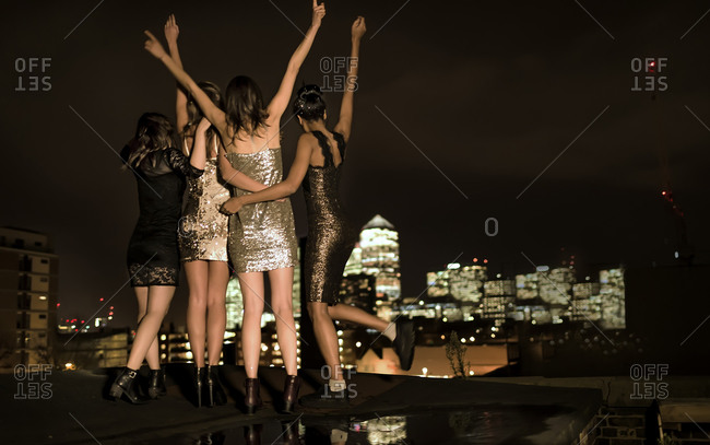 Friends in party dresses standing on a city rooftop celebrating