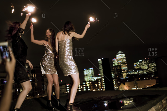 Friends hanging out on a city rooftop at night celebrating with sparklers