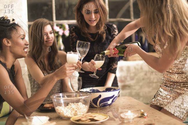 Woman pouring champagne for her friends at a party