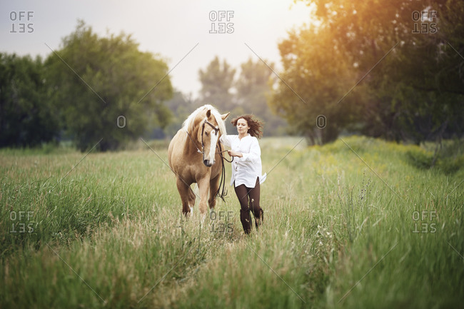 Woman walking in a field with her horse
