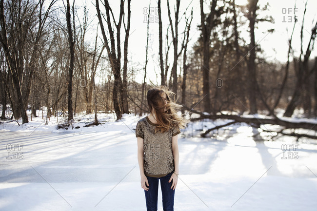 Young woman standing in the snow without a jacket