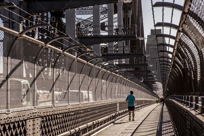 Sydney, Australia - May 13, 2015: Man jogging across Sydney Harbour Bridge