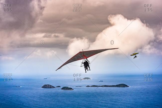 Tandem hang gliders soar above the ocean in Rio de Janeiro