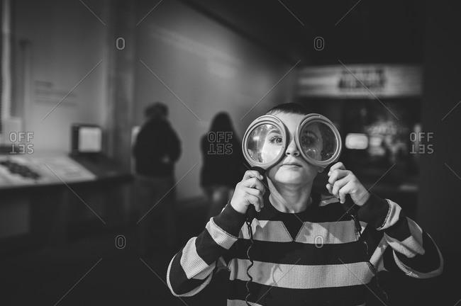 Boy holding magnifying glasses up to both eyes