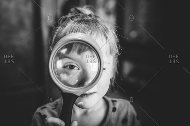 Young girl's eye enlarged in a magnifying glass