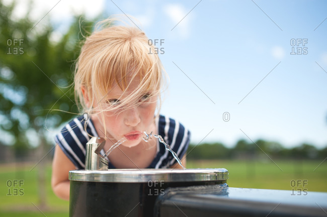 Young girl getting drink from outdoor water fountain