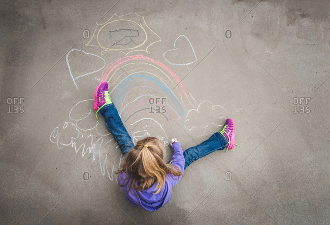 Overhead view of young girl drawing with chalk on pavement
