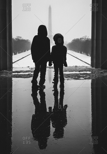 Two young children silhouetted before the Washington Monument