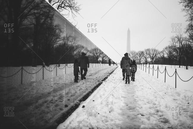 Family walking along the Vietnam Memorial in the snow