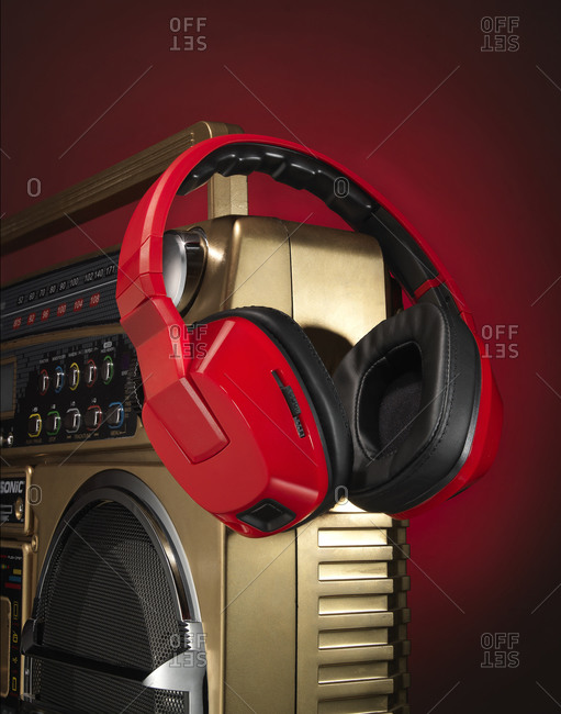 Close-up of red headphones hanging on the edge of a vintage boombox