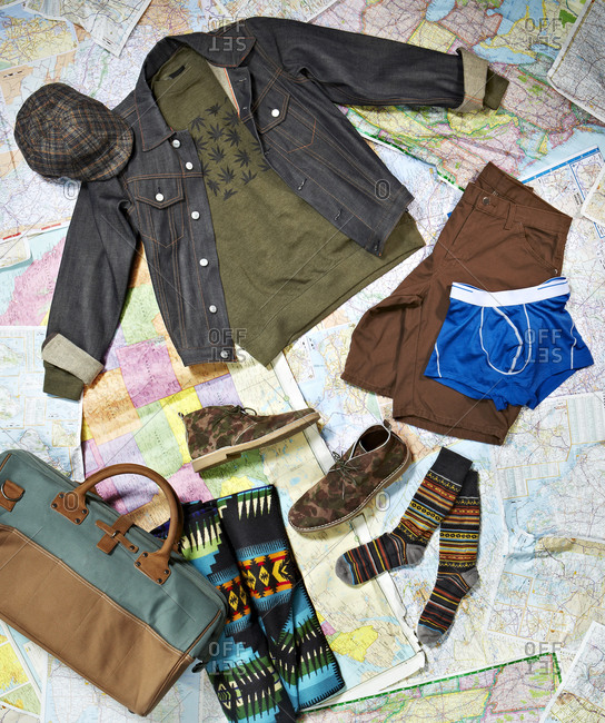 Men's clothing and travel bag arranged on a background of maps