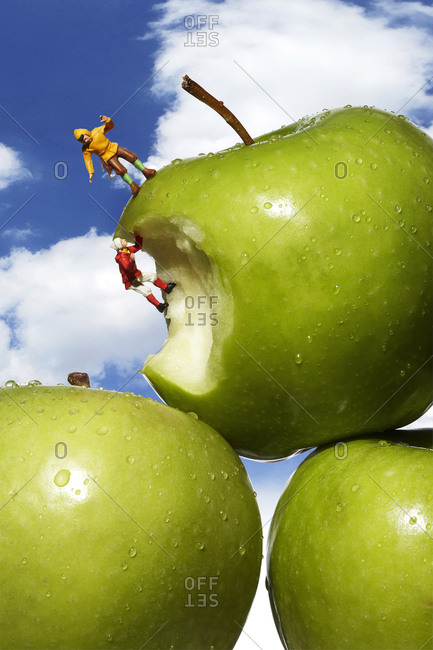Green apples with toy mountain climber figures