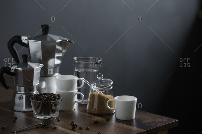 Moka coffee pot and coffee cups on a wood table with raw sugar and coffee beans