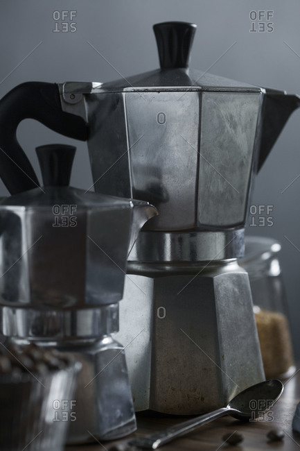 Moka coffee pot on a wood table with raw sugar and coffee beans