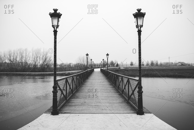 Bridge with lampposts over a partially frozen lake