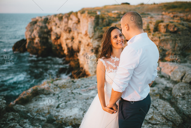 Bride and groom hold hands on cliffs at dusk
