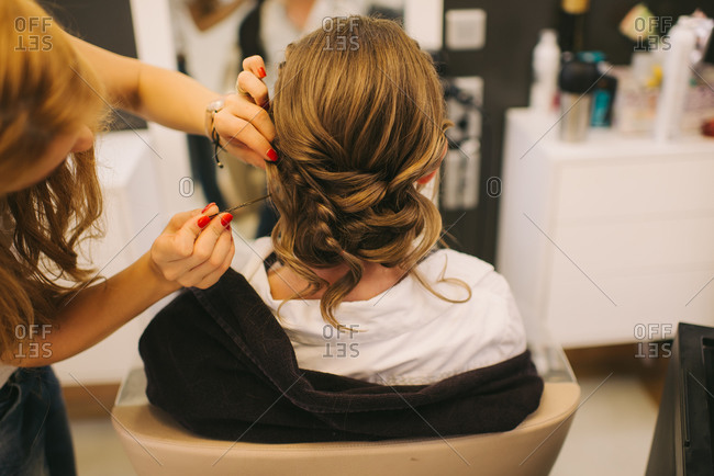 Hairdresser styling bride's hair for her wedding