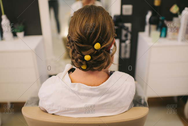 Bride with yellow balls in her hair sitting in salon chair