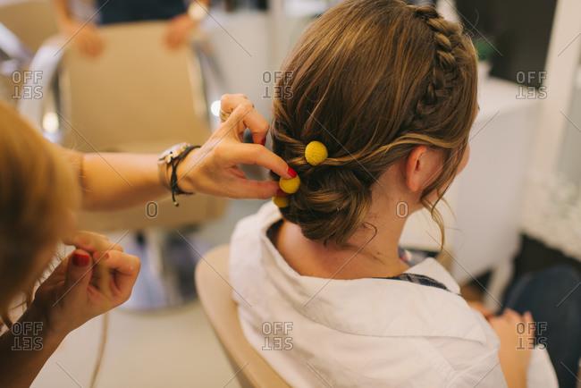 Hairdresser putting yellow balls in bride's hair
