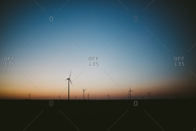 Silhouette of wind turbines at sundown