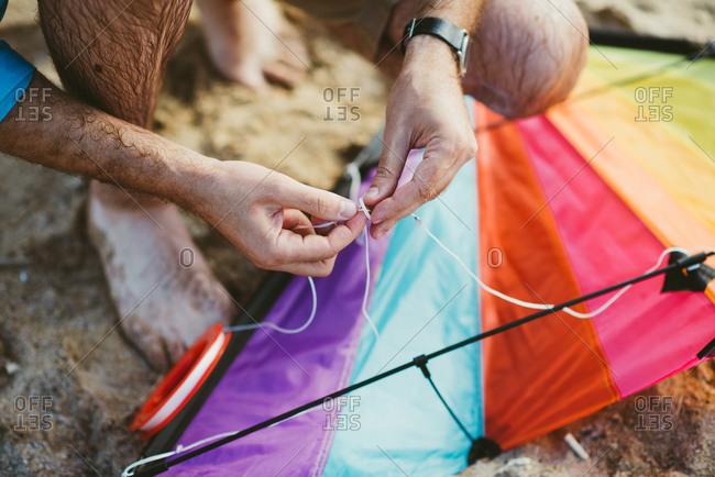 Man tying sting onto kite on a beach