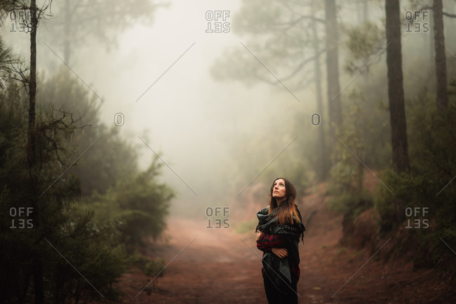 Woman gazing up in foggy forest